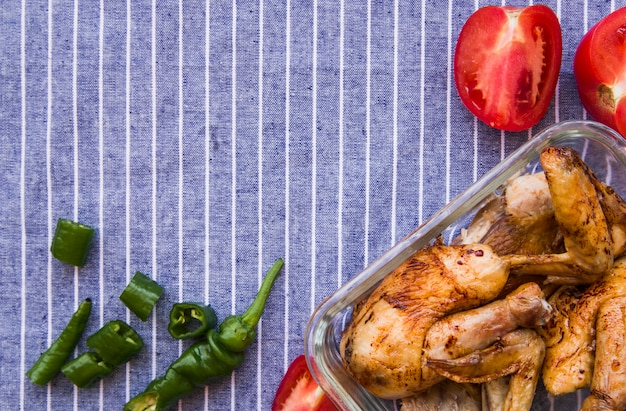 Overhead view of roasted chicken wings with tomato and green chilies against blue table cloth Free Photo