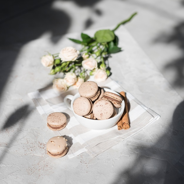 An overhead view of rose bouquet with cinnamon macaroons in white cup on grey concrete textured backdrop Free Photo