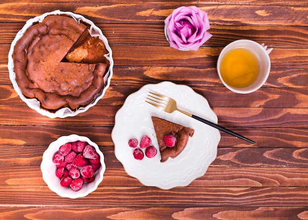 An overhead view of rose; herbal tea; cake slice and raspberry on wooden textured background Free Photo