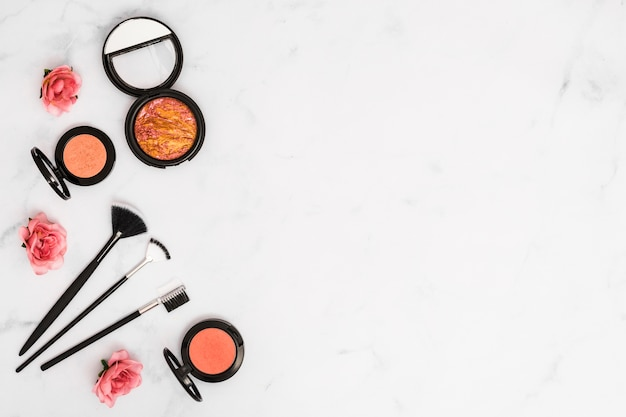 An overhead view of roses with compact face powder and makeup brushes on white background Free Photo