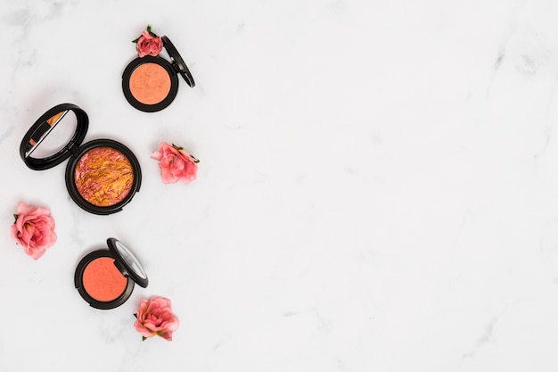 An overhead view of roses with compact face powder on white background Free Photo