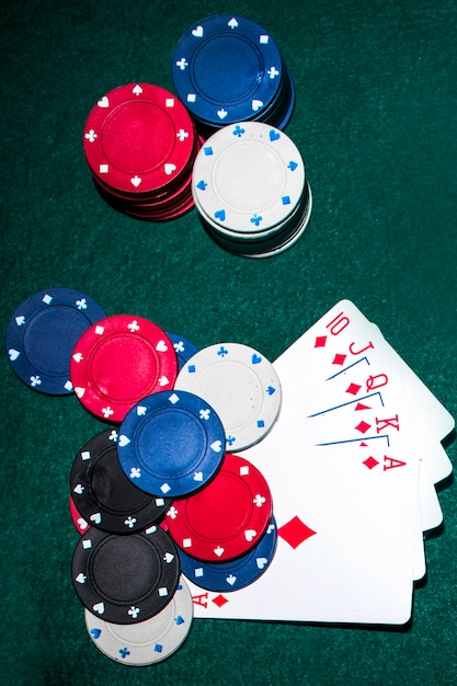 Overhead view of royal flush card and casino chips on poker table Free Photo
