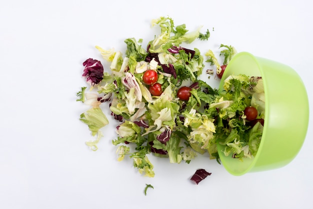 Overhead view of salad fallen from green bowl against white backdrop Free Photo