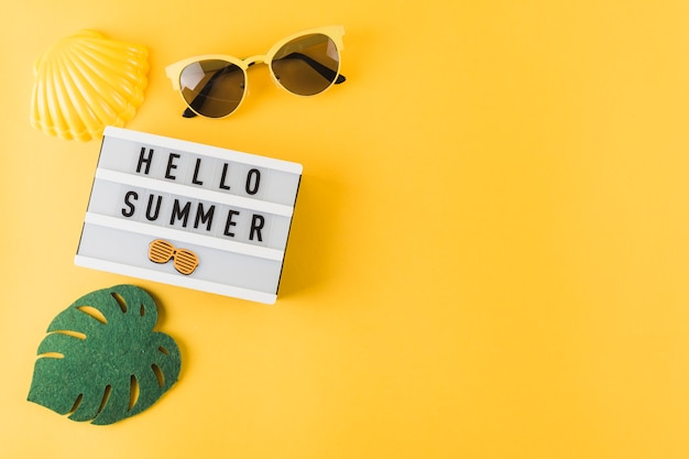 An overhead view of scallop; sunglass; leaf and hello summer light box on yellow backdrop Free Photo