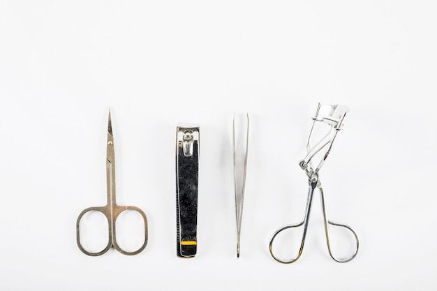 Overhead view of scissors; nail clipper; tweezer and eyelash curler on white background Premium Photo