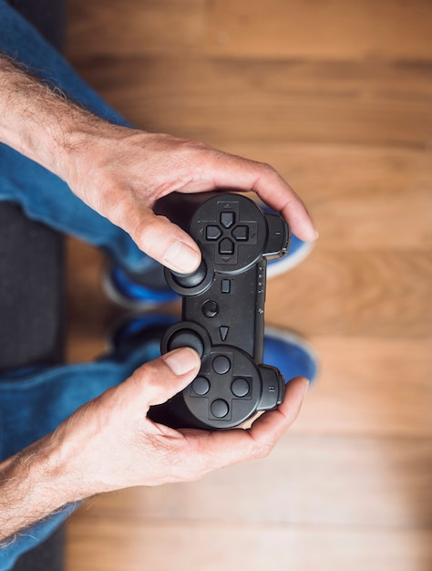 An overhead view of senior man's hand holding video game console Free Photo