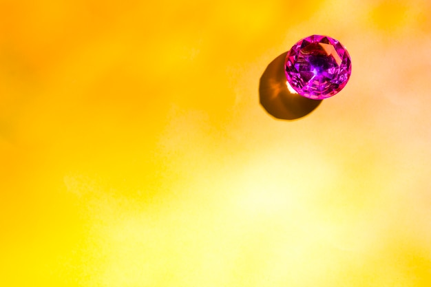 An overhead view of shiny ruby diamond on yellow background Free Photo