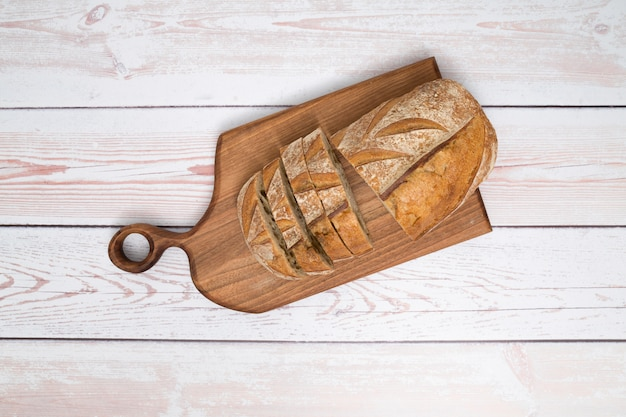 An overhead view slices of bread on chopping board over the wooden plank background Free Photo