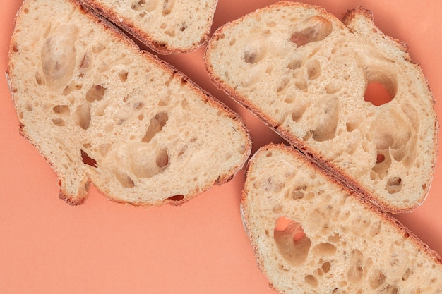 An overhead view slices of fresh bread on colored backdrop Free Photo