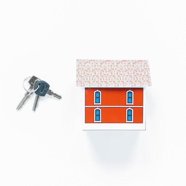 Overhead view of small house model and keys on white surface Free Photo