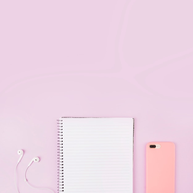 Overhead view of smartphone; earphone and notepad at the edge of pink background Free Photo