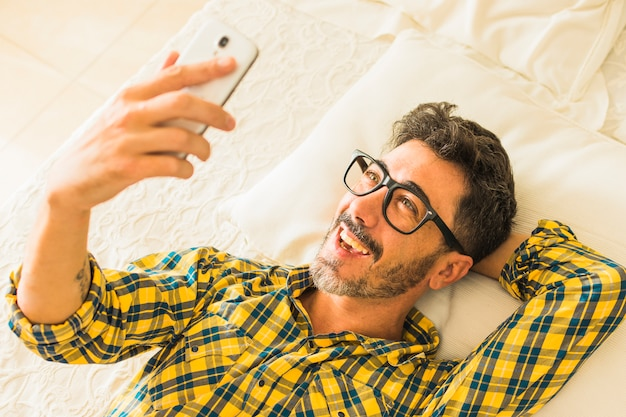 An overhead view of a smiling man lying on bed looking at smartphone Free Photo