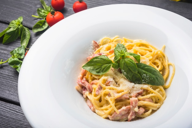 An overhead view of spaghetti with basil leaf and cheese toppings on white plate Free Photo