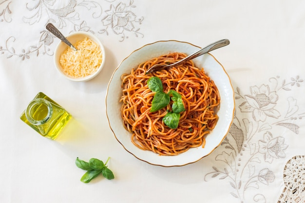 An overhead view of spaghetti with cheese bowl; basil and olive oil on tablecloth Free Photo