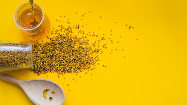 An overhead view of spilled bee pollens; honey pot and smiley wooden spoon on yellow backdrop Free Photo