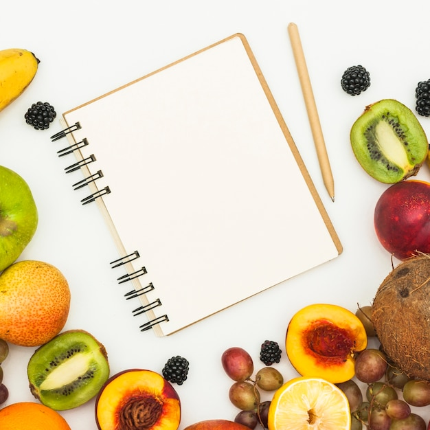 An overhead view of spiral notepad; pencil and various fruits on white backdrop Free Photo