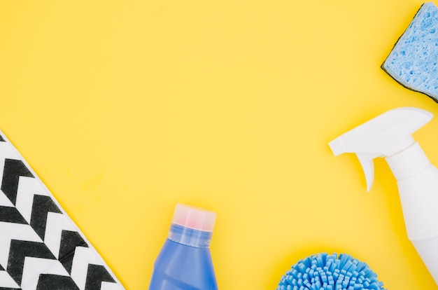 An overhead view of spray bottle and sponge on yellow backdrop Free Photo