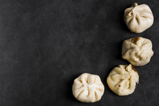 An overhead view of steam dumplings on black texture background Free Photo