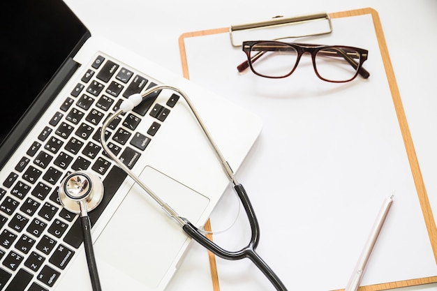 Overhead view of stethoscope on an open laptop with clipboard and eyeglasses on white background Free Photo