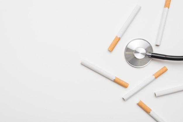 Overhead view of stethoscope with cigarettes over isolated on background Free Photo