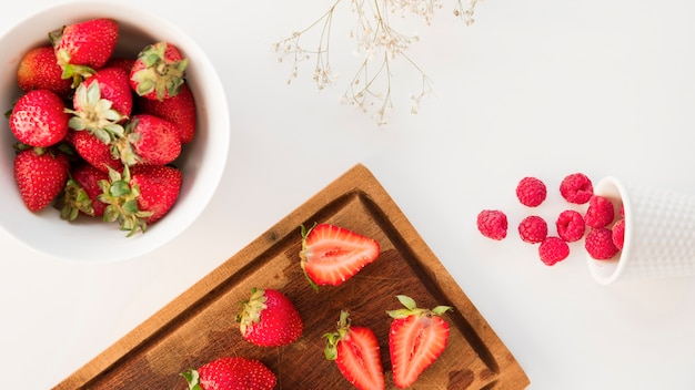 An overhead view of strawberries; and raspberries with gypsophila flower isolated on white background Free Photo