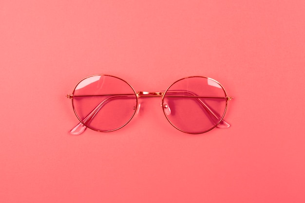 An overhead view of sunglasses on coral background Free Photo