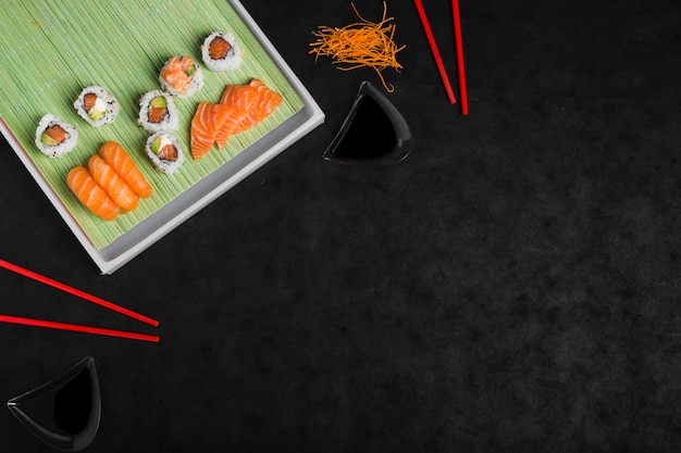 An overhead view of sushi roll with grated carrot and red chopsticks against black backdrop Free Photo