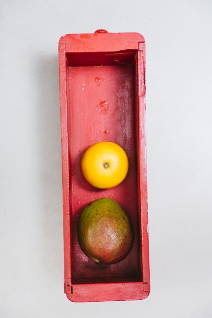Overhead view of sweet lime and mango in wooden container Free Photo
