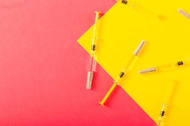 Overhead view of syringe over yellow and red background Free Photo