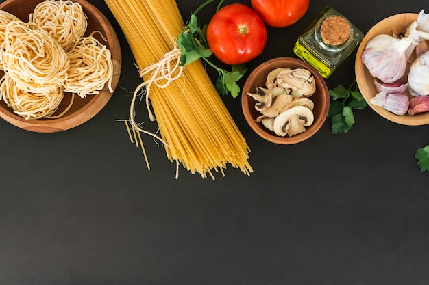 An overhead view of tagliatelle and spaghetti pasta with ingredients on black background Free Photo
