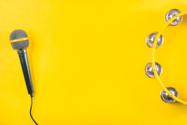 An overhead view of tambourine with microphone on yellow background Free Photo
