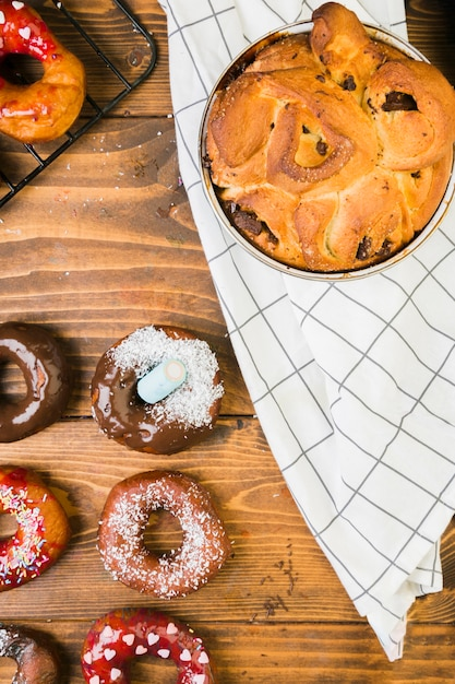 Overhead view of tasty dessert and chocolate donut on wooden desk Free Photo