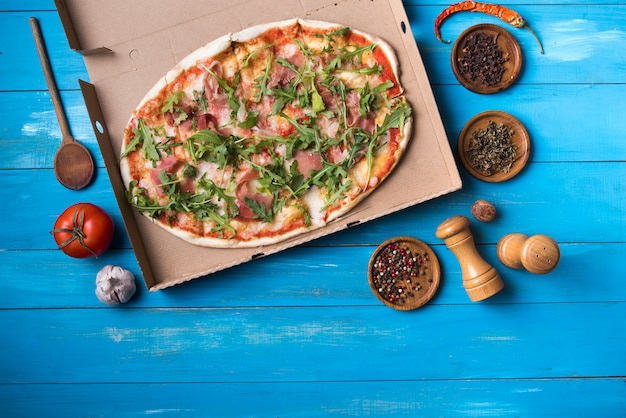 Overhead view of tasty pizza with ingredients on blue wooden table Free Photo