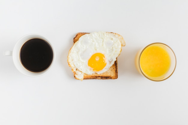 An overhead view of tea cup; juice glass and toast bread with fried egg isolated on white backdrop Free Photo