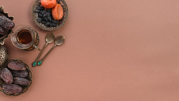 An overhead view of tea glass; dried fruits; dates and metallic spoons on brown backdrop Free Photo