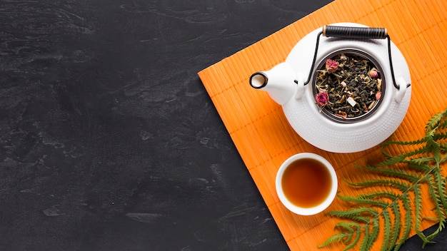 Overhead view of tea herb and teapot with fern leaves on orange placemat over black backdrop Free Photo