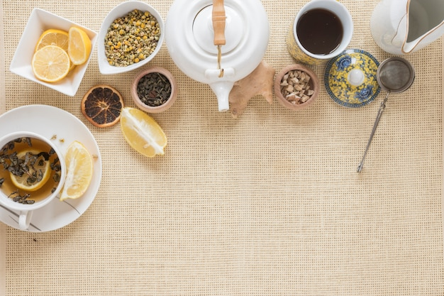 Overhead view of teapot; tea strainer; lemon slice; dry grapefruit and dried chinese chrysanthemum flowers on placemat Free Photo