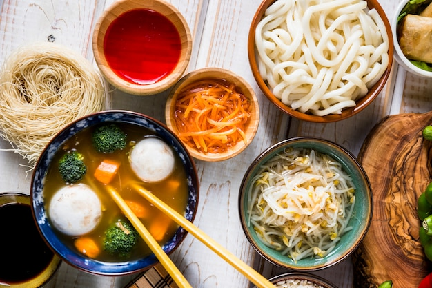 An overhead view of thai fish and vegetable bowl soup with udon noodles; sauce and beans sprouts on white desk Free Photo
