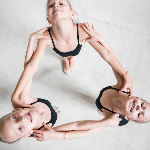 Overhead view of three ballerina girls holding each other's shoulder looking up Free Photo