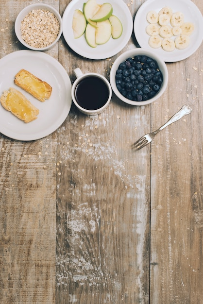 An overhead view of toast; oats; blueberries; coffee cup; apple and banana slices on table Free Photo