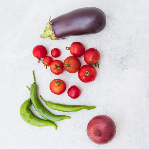 An overhead view of tomatoes; green chilies; onion and eggplant on white textured background Free Photo