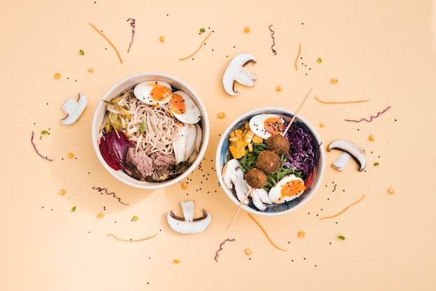 An overhead view of traditional asian cuisine bowls decorated with mushroom and sesame seeds on colored backdrop Free Photo
