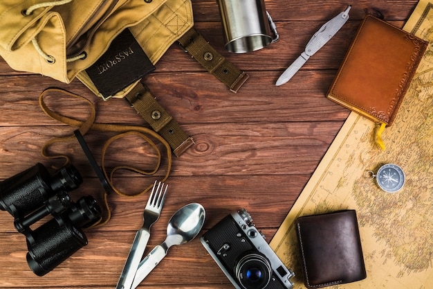 Overhead view of travelling equipments over wooden desk Free Photo
