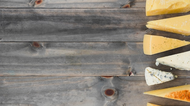 An overhead view of triangular cheese wedges on wooden table Free Photo