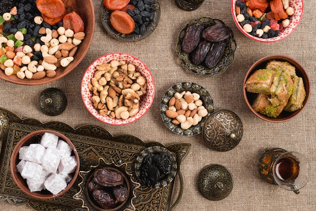 An overhead view of turkish tea; dates; lukum; dried fruits and nuts on jute tablecloth Free Photo