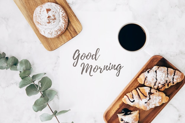 An overhead view of twig; coffee; bun and croissants with good morning message over marble texture backdrop Free Photo