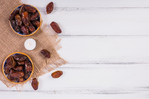 An overhead view of two bowls with ripe juicy dates on white wooded table Free Photo