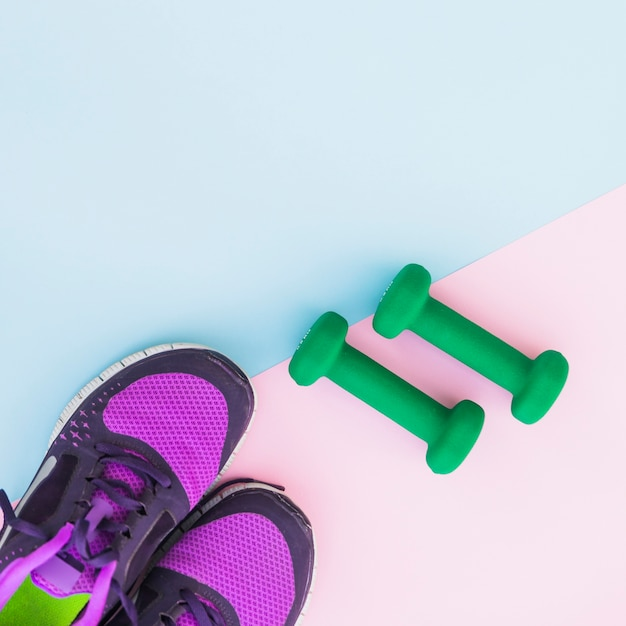An overhead view of two green dumbbells and pair of shoes on dual background Free Photo