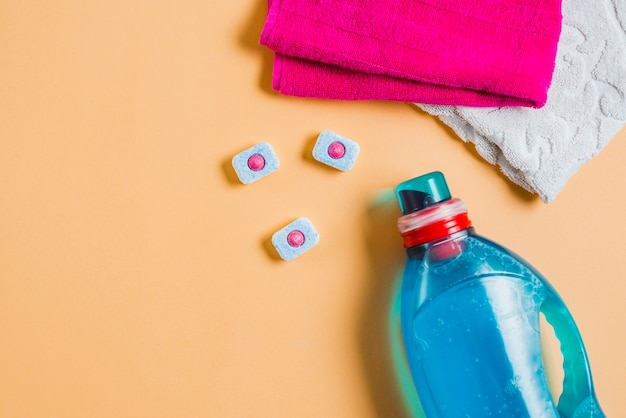 An overhead view of two towels and liquid detergent with dishwasher tablets Free Photo