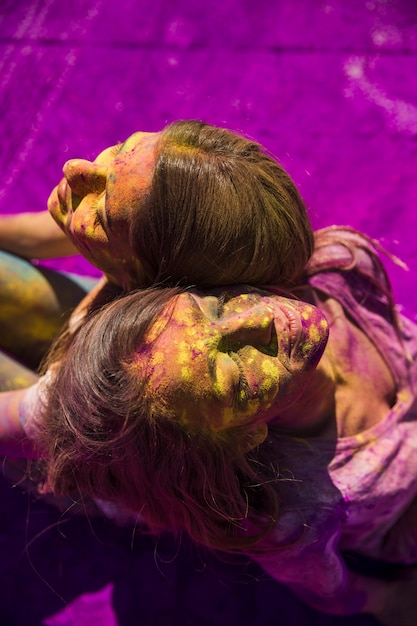 An overhead view of two women sitting back to back with holi color on their face Free Photo
